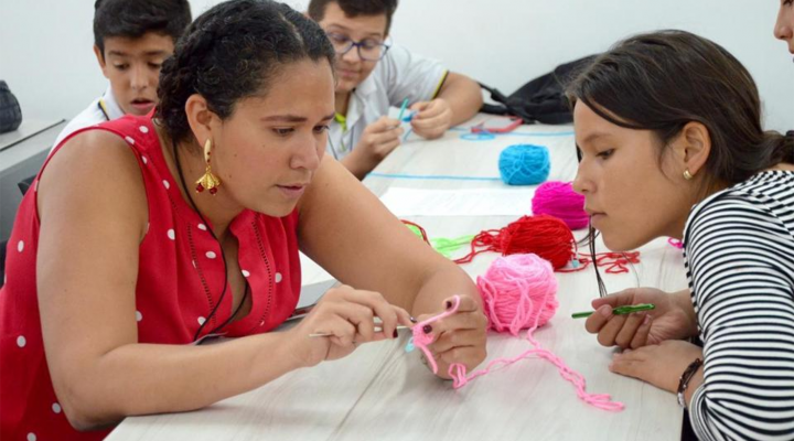 Ana Maria Porras crochets with a student doing an event of Clubes de Ciencia in Bucaramanga, Colombia