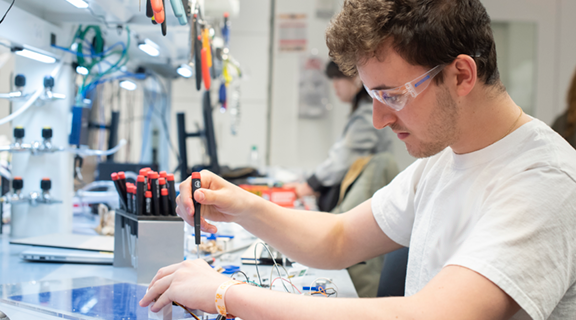 student in lab working on electronics